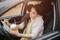 Pretty woman eating food and driving in her car. Fall vacation, holidays, travel, road trip and people concept royalty free stock images