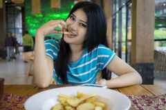 Pretty woman eating french fries at cafe Stock Images