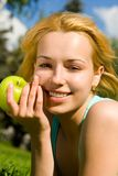 Pretty woman eating green apple Stock Photography