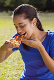 Pretty woman eating pizza in the park Stock Images