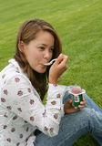Pretty Woman Eating Yogurt. A pretty woman eating yogurt on the grass Stock Photo