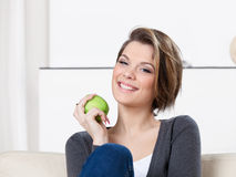 Pretty woman eats a green apple Royalty Free Stock Photography