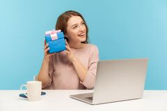 Pretty woman employee sitting at workplace and holding gift near ear, listening with interest what`s inside box