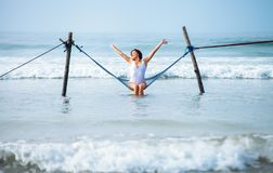 Pretty woman enjoy with ocean breeze and sun sits in hammock swi. Ng over the waves Stock Photography