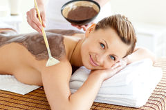 Pretty woman enjoying a beauty treatment with mud Stock Images