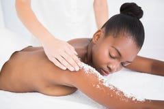 Pretty woman enjoying an exfoliation massage Stock Photo