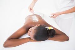 Pretty woman enjoying an exfoliation massage Stock Photography