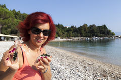 Pretty woman enjoying fresh Mediterranean scampi. Cute middle-aged woman enjoying fresh, raw Mediterranean scampi, outside on the sunny autumn beach, high Stock Images