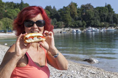 Pretty woman enjoying fresh sea food sandwich Stock Photos