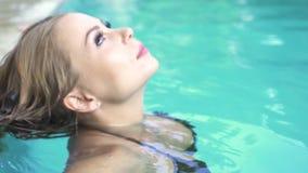 Pretty woman enjoying fresh water in swimming pool at hot sunny day. Portrait beautiful woman in black bikini relaxing. In outdoor pool in summer resort. Happy stock video