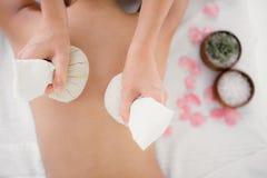 Pretty woman enjoying a herbal compress massage Royalty Free Stock Photos
