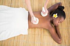 Pretty woman enjoying a herbal compress massage Stock Photo