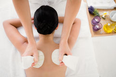 Pretty woman enjoying a herbal compress massage Royalty Free Stock Images