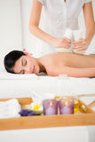 Pretty woman enjoying a herbal compress massage Stock Photos