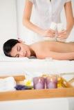 Pretty woman enjoying a herbal compress massage Stock Photos