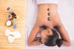 Pretty woman enjoying a hot stone massage Royalty Free Stock Photo