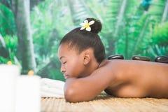 Pretty woman enjoying a hot stone massage Royalty Free Stock Photos