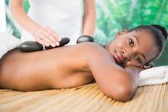 Pretty woman enjoying a hot stone massage Royalty Free Stock Images