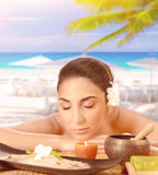 Pretty woman enjoying massage on the beach Stock Images