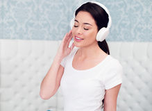 Pretty Woman Enjoying Music Using Headphones Royalty Free Stock Images