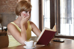 Pretty woman enjoying reading book at coffee shop drinking cup of coffee or tea smiling happy Stock Photography