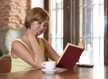 Pretty woman enjoying reading book at coffee shop drinking cup of coffee or tea smiling happy Stock Images