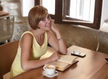 Pretty woman enjoying reading book at coffee shop drinking cup of coffee or tea smiling happy Stock Image