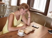 Pretty woman enjoying reading book at coffee shop drinking cup of coffee or tea smiling happy. Young pretty woman enjoying reading book at coffee shop drinking Stock Images