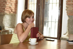 Pretty woman enjoying reading book at coffee shop drinking cup of coffee or tea smiling happy. Young pretty woman enjoying reading book at coffee shop drinking Royalty Free Stock Photography