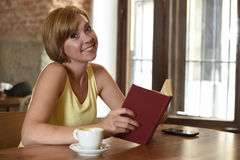 Pretty woman enjoying reading book at coffee shop drinking cup of coffee or tea smiling happy Stock Photos