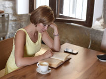 Pretty woman enjoying reading book at coffee shop drinking cup of coffee or tea smiling happy. Young pretty woman enjoying reading book at coffee shop drinking Royalty Free Stock Images
