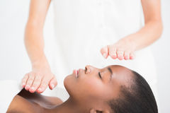 Pretty woman enjoying a reiki technique. At the health spa stock image