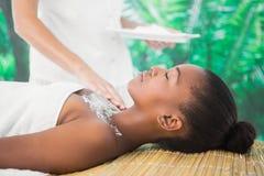 Pretty woman enjoying a salt scrub massage. Side view of a pretty woman enjoying a salt scrub massage on the chest Stock Photos