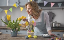 Pretty woman is enjoying scent of flowers. Smiling lady smelling beautiful tulips while preparing for easter dinner at home royalty free stock images