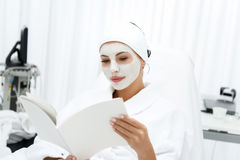 Pretty woman enjoying skin care treatment at spa. Healthy girl is resting at beauty salon. She is sitting in bathrobe and reading magazine with interest. Lady Stock Photography