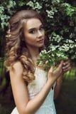Pretty woman enjoying smell flowers Stock Photos