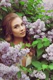 Pretty woman enjoying smell lilac flowers Royalty Free Stock Photo