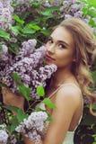 Pretty woman enjoying smell lilac flowers Stock Photo