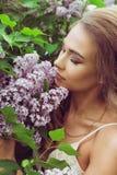 Pretty woman enjoying smell lilac flowers Royalty Free Stock Image
