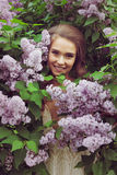 Pretty woman enjoying smell lilac flowers Royalty Free Stock Photos