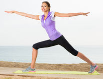Pretty woman exercising yoga poses on beach Royalty Free Stock Image