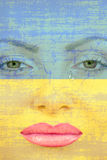 Pretty woman face with tear on Ukranian flag background. Stock Photo