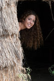 Pretty woman facing the camera through a straw house door Royalty Free Stock Photography
