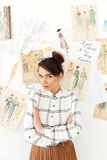 Pretty woman fashion illustrator. Picture of young pretty woman fashion illustrator standing near a lot of illustrations. Looking at camera with arms crossed royalty free stock photography