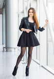 Pretty woman in fashion style. Young female model indoor full-length portrait wearing leather jacket and black skirt. Fashion lady with long brown hair wear Royalty Free Stock Photos