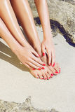Pretty woman feet and hands with red manicure Stock Photos