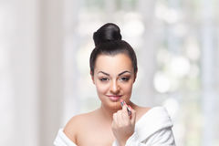 Pretty woman finishing her makeup with a lipstick Stock Photos