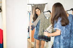 Pretty woman in a fitting room. Attractive young woman trying on a pretty dress in a fitting room at a fashion store Stock Image