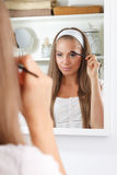 Pretty woman fixing her eyebrows Stock Images
