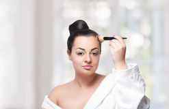 Pretty woman fixing her makeup with a brush Stock Photo